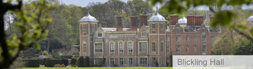 Blickling Hall country estate from a distance surrounded by trees on a sunny day